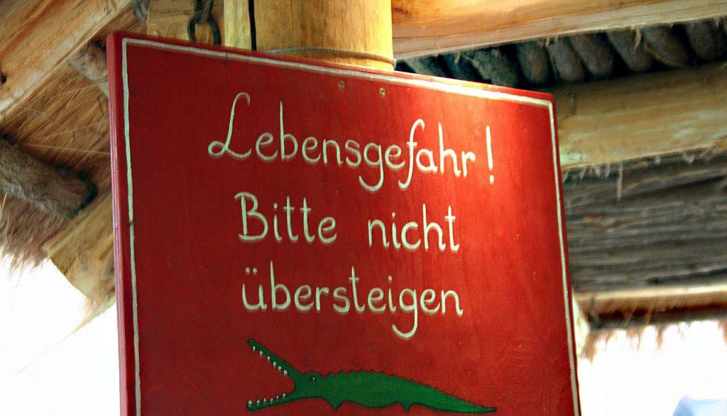 Warnschild vor einem Krokodilgehege im Zoo von Hagenbeck