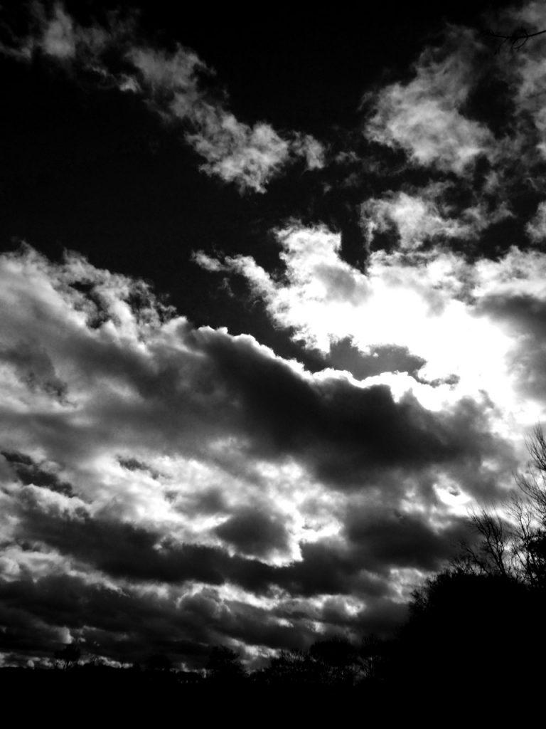 Wolkenbilder über einem Stoppelfeld in Ahrbergen in schwarz-weiß