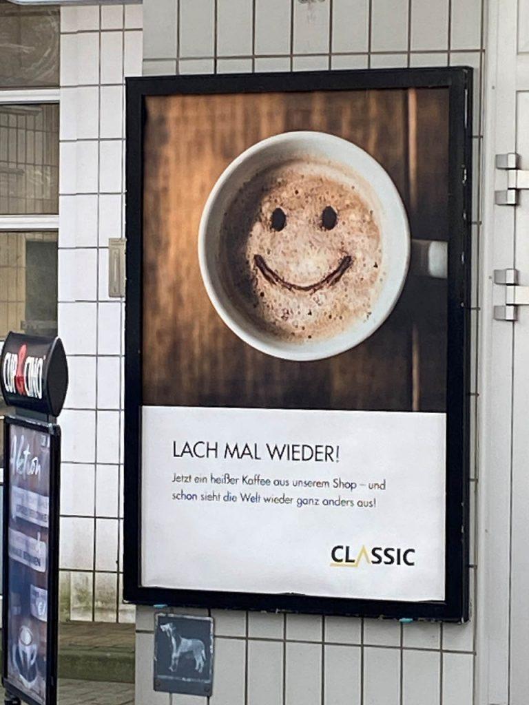 """Tankstellenschild mit der Auffordung einen Kaffee zu trinken und """"Lach mal wieder"""""""