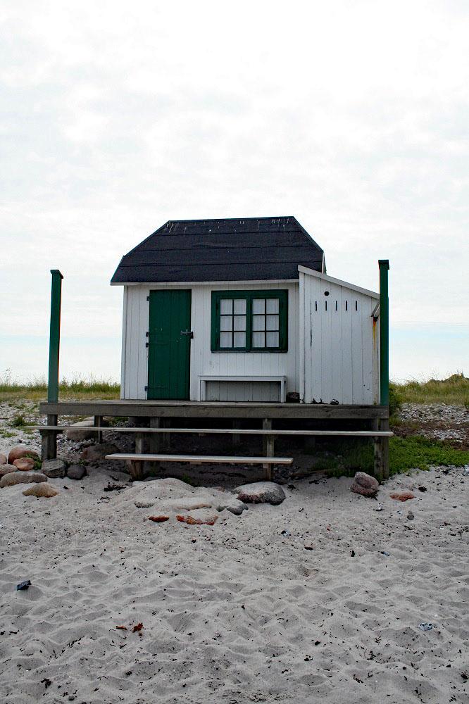 T in die neue Woche mit einem Strandhaus auf Aero in Dänemark mit grünen Fenster und einer grünen Tür. Ostseestrand