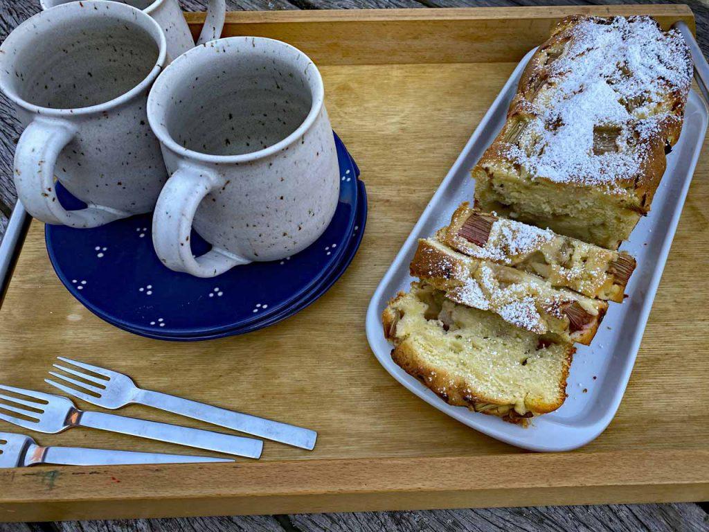 Rhabarberjoghurtkuchen auf dem gedeckten Tisch mit Tassen, Kuchentellern und Kuchengabeln. Guten Appetit
