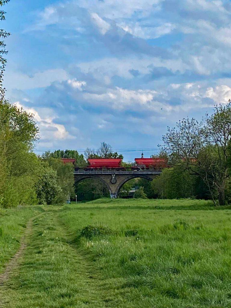 Eisenbahnbrücke mit roten Güterwagen. Von hinten nach vorne gelesen wird aus Tor - Rot