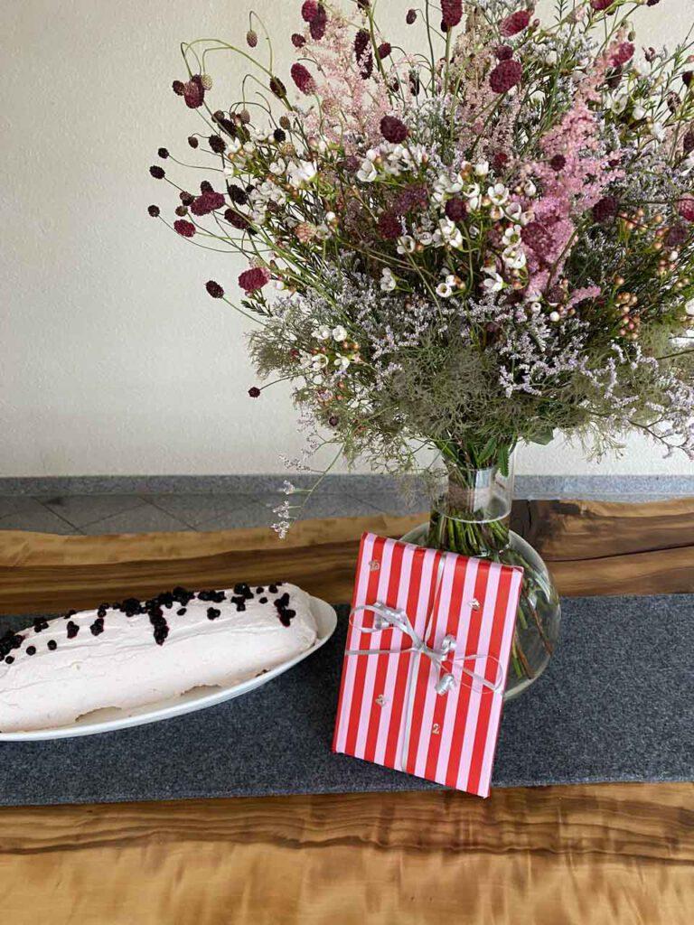 Geburtstagstisch mit Blumen, Kuchen und Geschenk