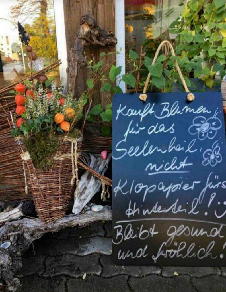 Verkaufsschild vor einem Blumenladen mit Blumen statt Klopapier